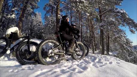 Kaksi Fatbike-pyöräilijää lumisessa maastossa.