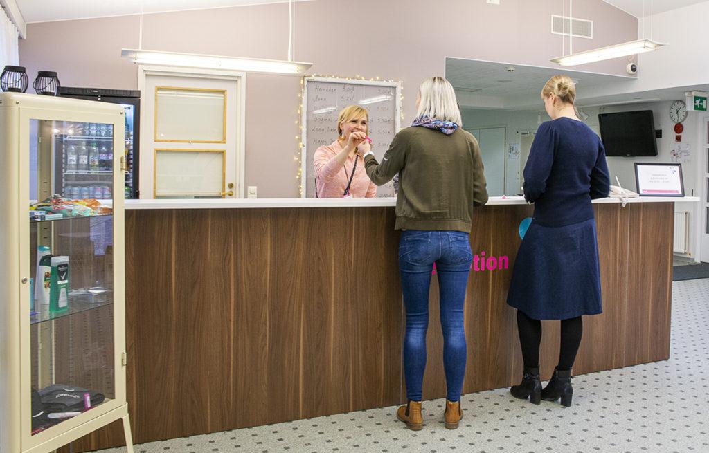 Vastaanotossa nainen antaa huoneen avaimen asiakkaalle.