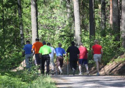 Ryhmä ihmisiä sauvakävelemässä metsässä.