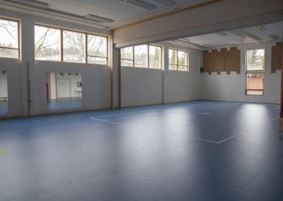 Liikuntasali Vilhelmiina, jossa sininen lattia ja ikkunat seinän yläosassa.