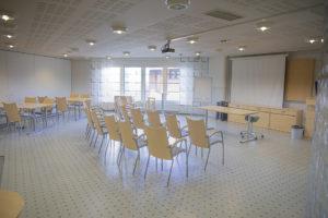 Kokoustila Tähkässä tuolirivit, pöytäryhmä ja ikkuna.