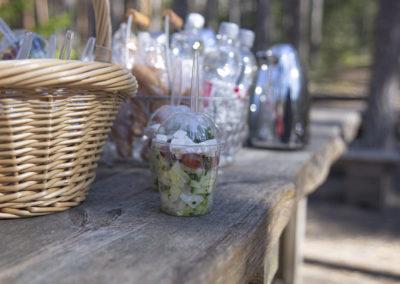 Retkisalaatti pakattuna muovirasiaan, jonka taustalla juomapulloja ja termoskannu.