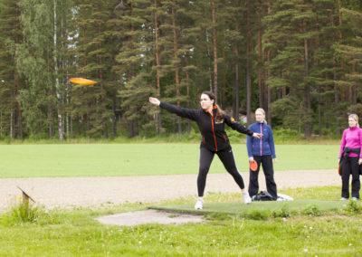 Nainen heittää frisbeegolfkiekkoa ja kaksi naista katselee vierestä.