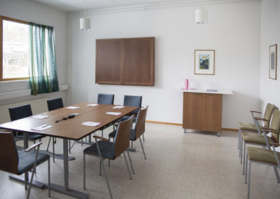 Kokoustila Koivussa neuvottelupöytä tuoleineen ja pieni kaappi takaseinällä.