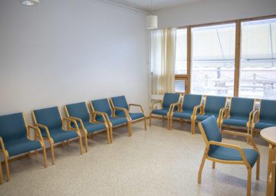 Ikkunallinen kokoustila Kataja, jossa tuolirivit seinien vieressä ja pieni pöytä.