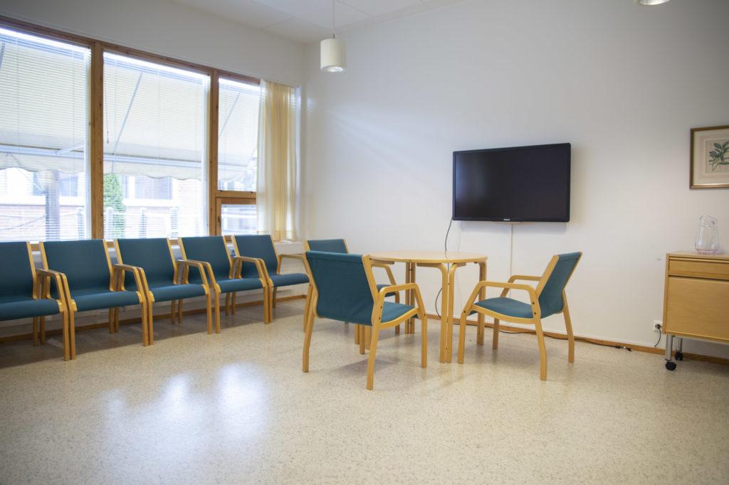 Ikkunallinen kokoustila Katajassa tuolirivit seinien vieressä, pieni pöytäryhmä ja TV-näyttö.