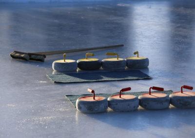 Curlingkiviä ja harja jäällä.