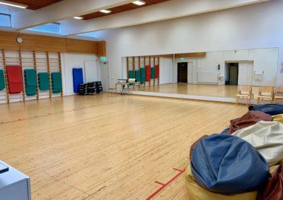 Liikuntasali Iso-Kustaassa on puulattia ja peiliseinä.