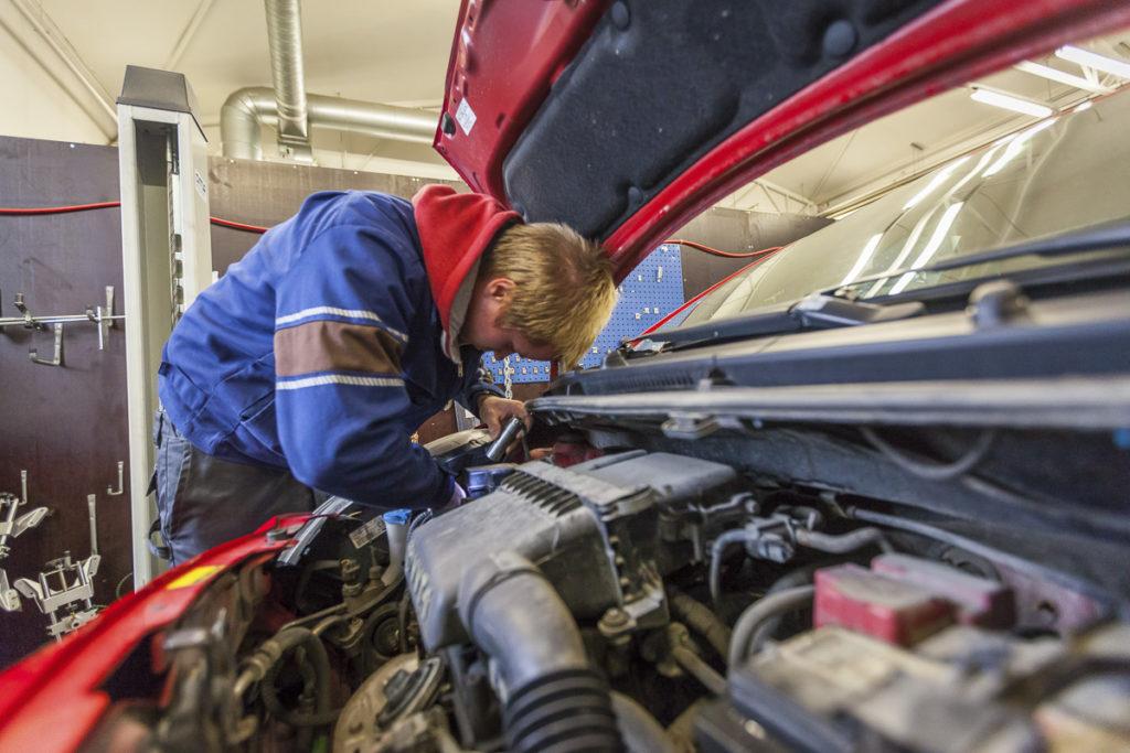 Opiskelija korjaa punaista autoa, jonka konepelti on auki.