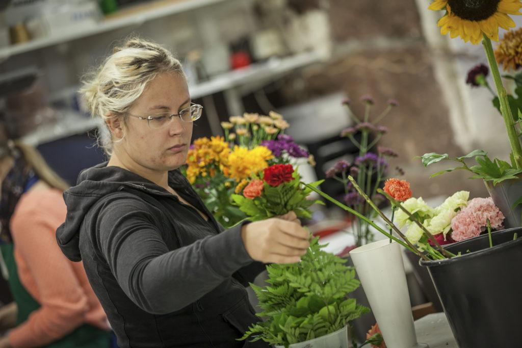 Nainen tekee värikästä kukkakimppua.