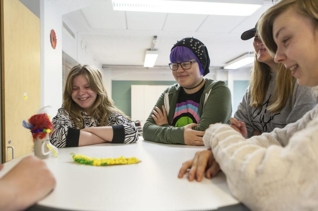 Neljä opiskelijanuorta pyöreän pöydän ääressä.