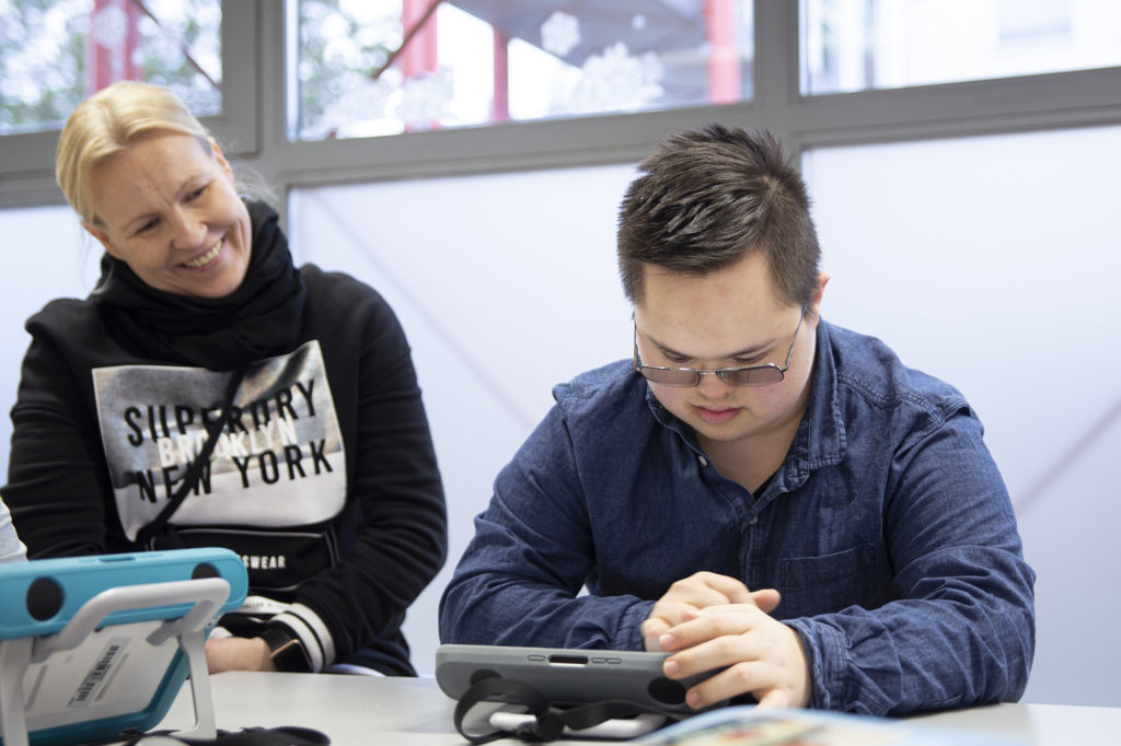 Opiskelija työpöydän ääressä tabletilla ja opettaja hymyilee vieressä.