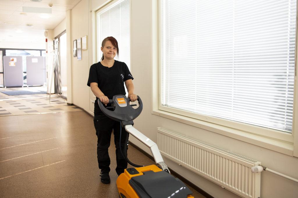 Nuori nainen pesee lattioita oranssin lattianpesukoneen avulla.