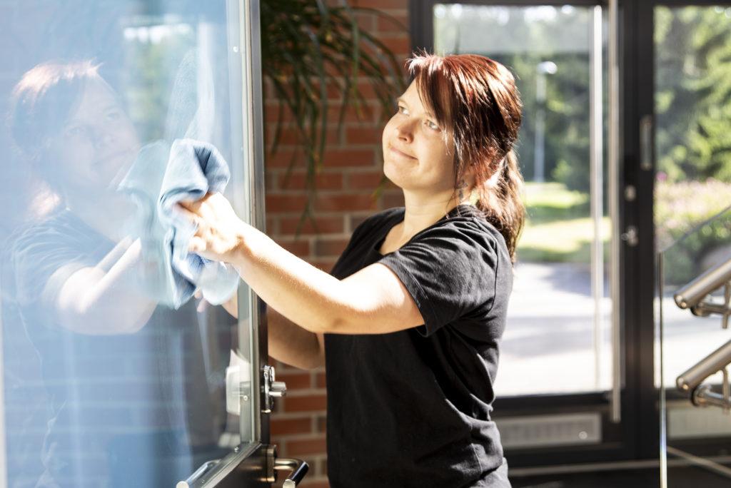 Nuori nainen pyyhkii sisäoven ikkunaan mikrokuituliinalla.