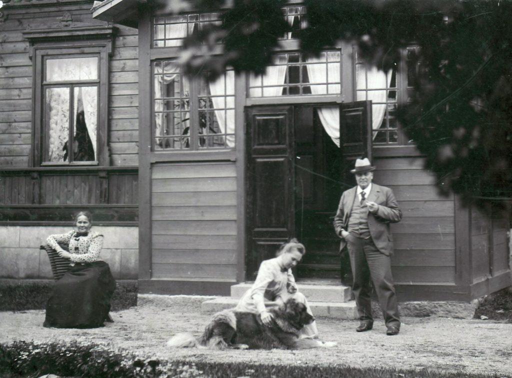 Vanhassa mustavalkoisessa kuvassa talon edessä Wilhelmiina Kiipula istuu tuolilla, Alma Kiipula silittää koiraa ja Kustaa Kiipula seisoo.