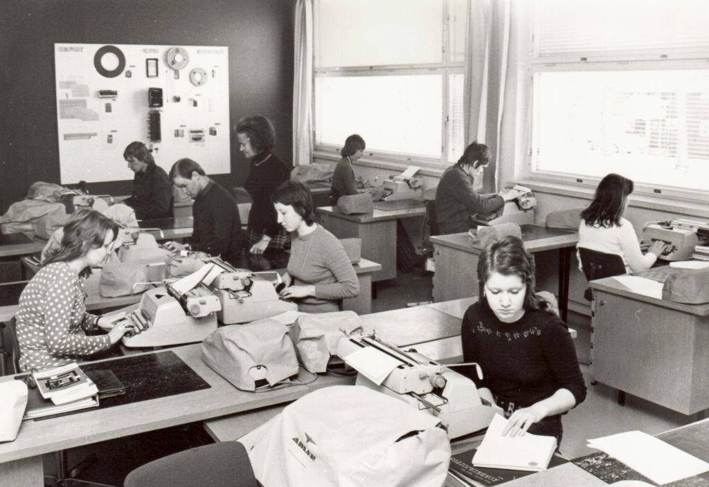 Vanhassa mustavalkokuvassa kahdeksan opiskelijaa opettelee luokassa konekirjoitusta.