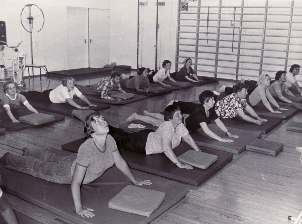 Mustavalkokuvassa 13 kuntoutujaa venyttelee patjojen päällä, vatsallaan maaten liikuntasalissa.