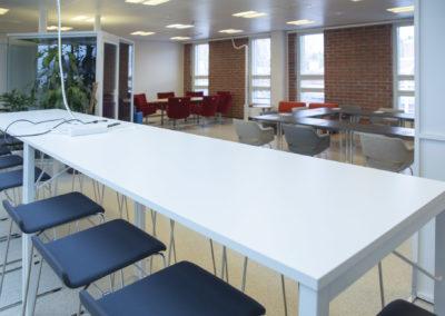 Kokoustila Maisemassa korkea kokouspöytä ja -tuolit, taustalla istumaryhmä ja kokouspöytä U-muodossa.