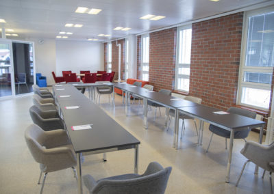 Kokoustila Maisemassa kokouspöytä U-muodossa ja tilan takana istumaryhmä.