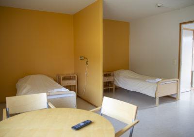 Guest Housen ulkosiiven majoitushuone, jossa kaksi 90 cm sänkyä ja levitettävä vuodesohva.
