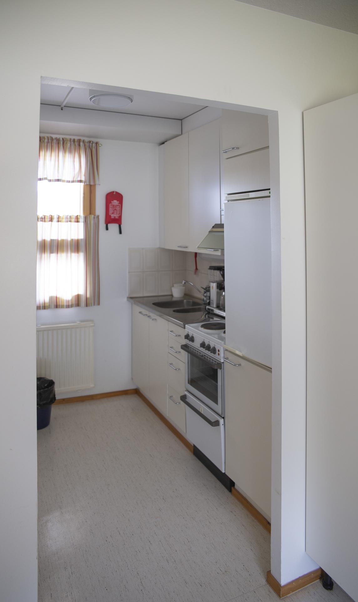 Guest Housen ulkosiiven majoitushuoneen keittiö.