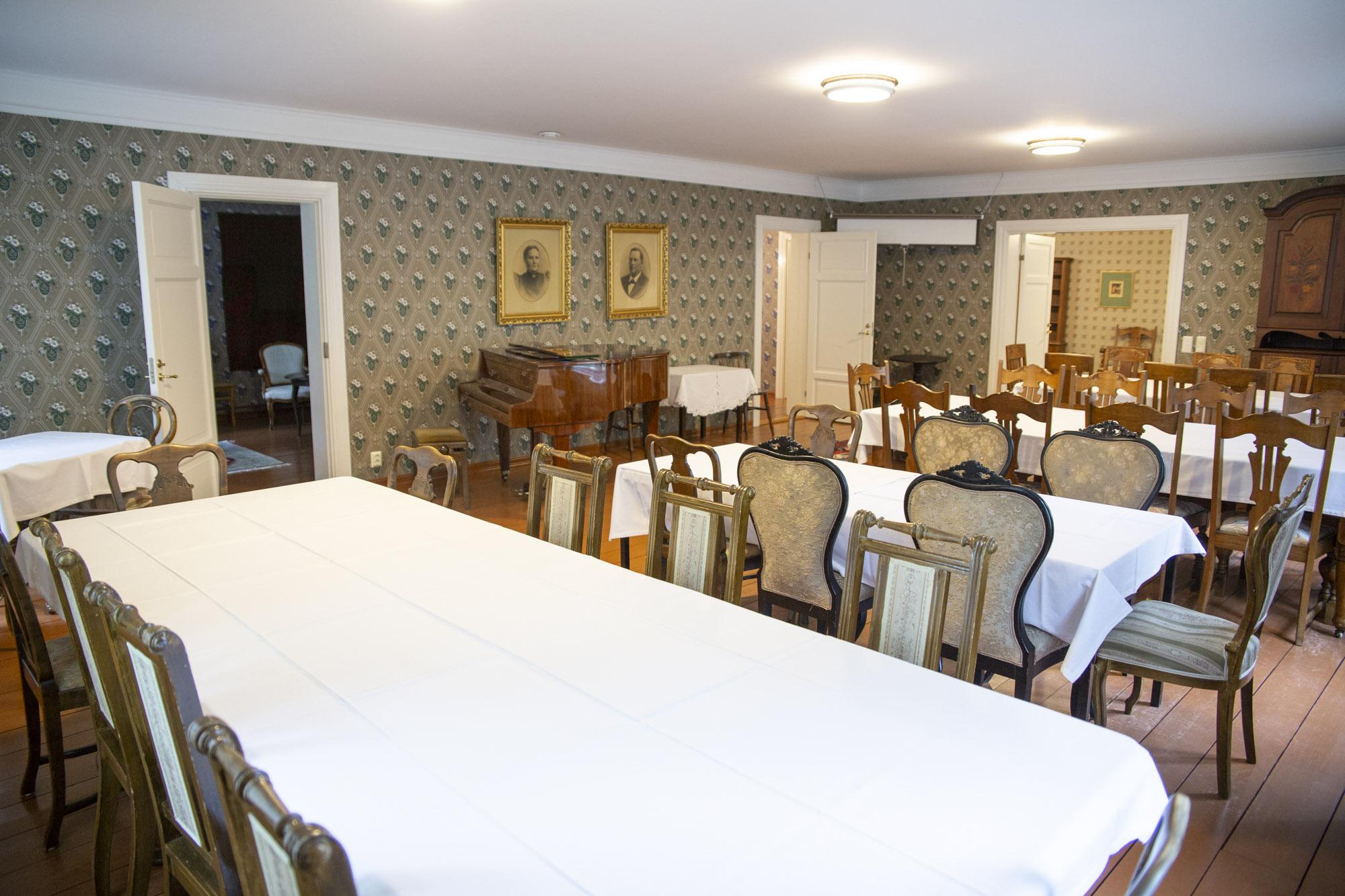 Ruokapöytiä joiden ympärillä tuoleja ja seinän vierellä flyygieli.