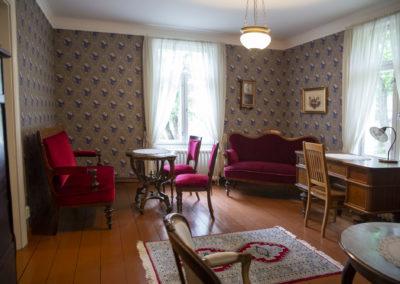 Huone jossa punainen sohvaryhmä ja seinän vierellä toinen punainen sohva.