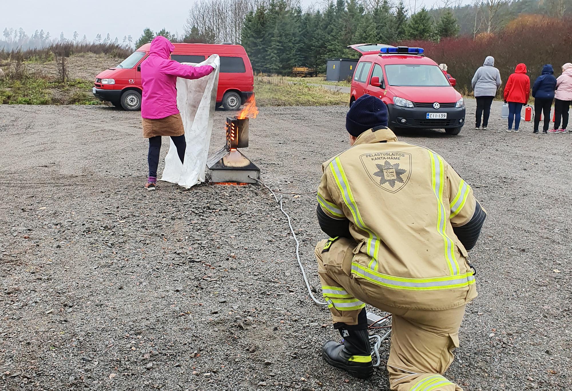 Nainen sammuttaa peitteellä tulipaloa.