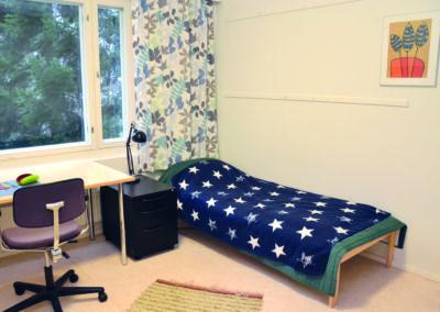 Opiskelija-asuntolan majoitushuone. jossa sänky, yöpöytä ja työpöytä sekä tuoli.