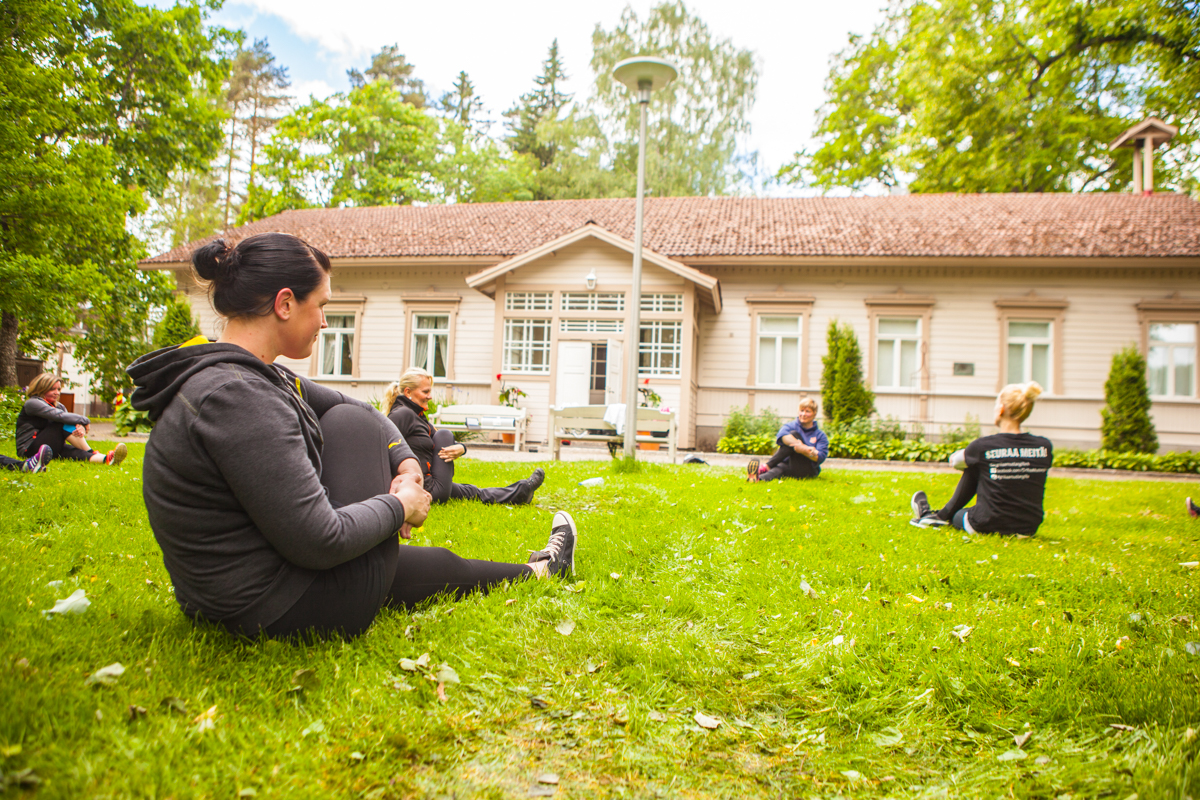 Ryhmä ihmisiä jumppaamassa nurmikolla.
