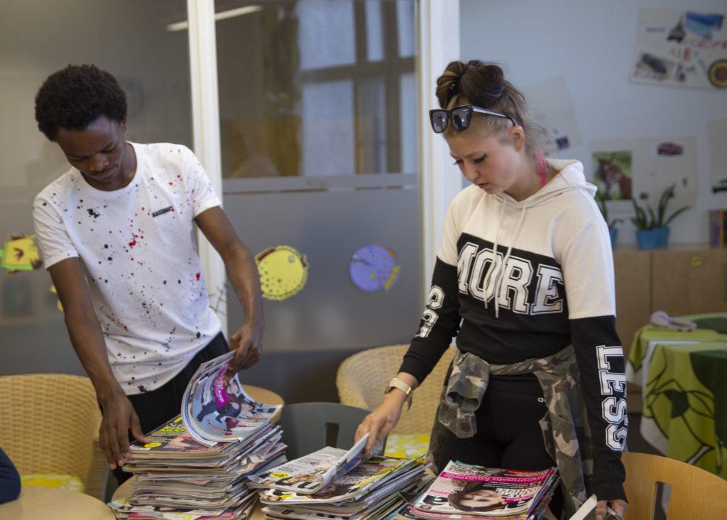 Kaksi opiskelijaa selaa luokassa pöydän ääressä aikakauslehtipinoja.