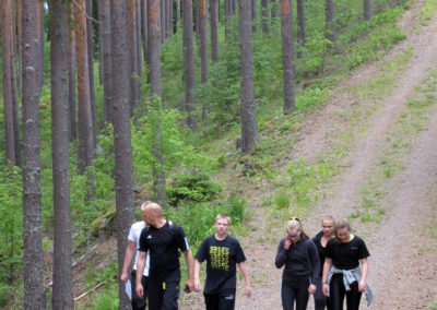 Leiriläisiä metsässä kävelyllä.