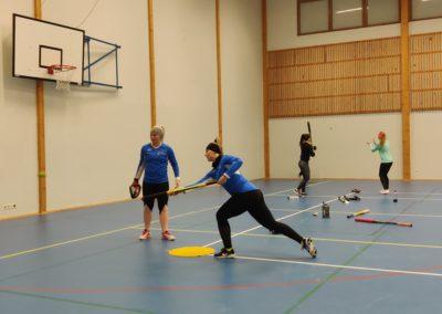 Nuoria naisia harjoittelemassa pesäpalloa liikuntahallissa.