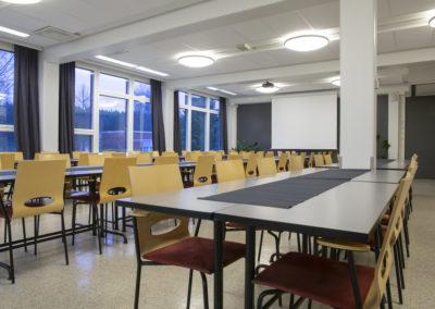 Kultatähkä 1 tilassa pitkät pöydät ja takaseinällä valkokangas.
