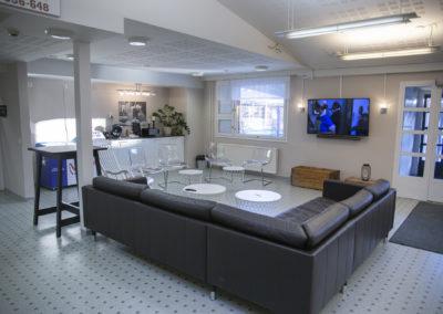 Kiipula Guest Housen vastaanoton aulatila, jossa sohvaryhmä, keinutuoli ja televisio..