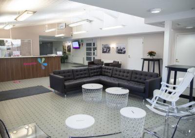 Kiipula Guest Housen vastaanotto ja aulatila, jossa sohvaryhmä, keinutuoli ja televisio..