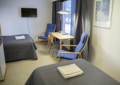 Kiipula Guest House kahden hengen huone, jossa 140 cm ja 100 cm leveät sängyt, wc, suihku ja televisio.