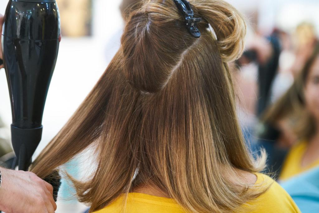 Kampaaja kuivaa naisen hiuksia hiustenkuivaajalla.