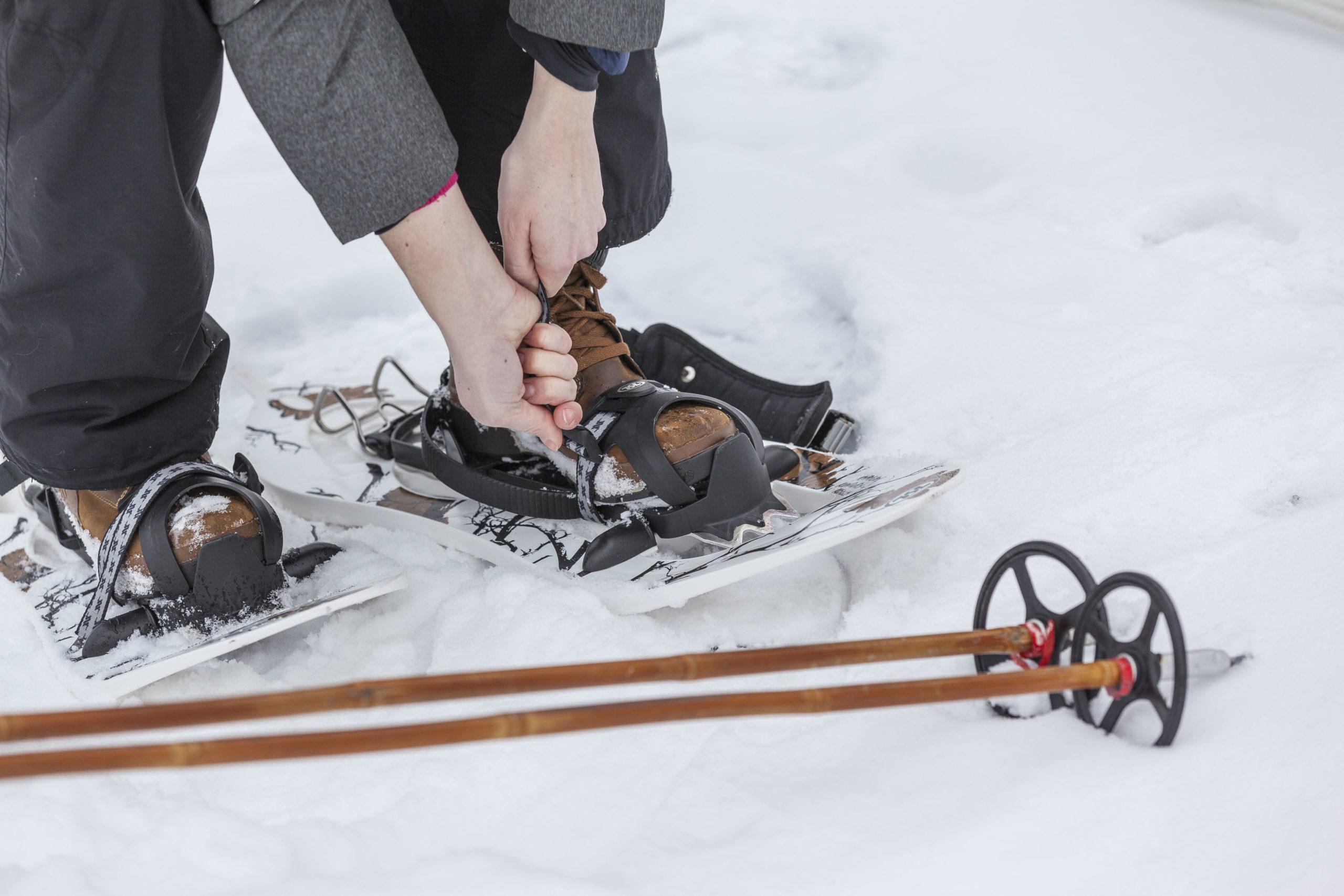 Nainen kiristää lumikenkien solkia, edustalla sauvat.