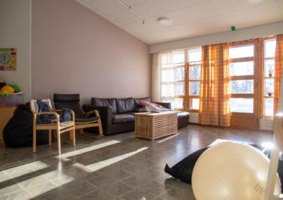 Asuntolan olohuone. sohva, nojatuoli, sohvapöytä.