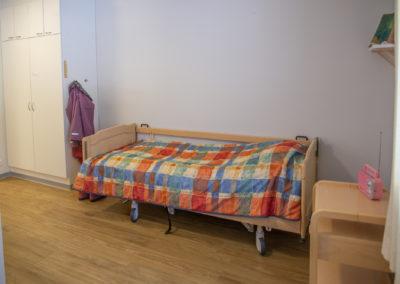 Asuntolahuone, sänky ja kaappi.