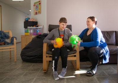 Asumisenohjaaja opiskelijan kanssa oleskeluhuoneessa.