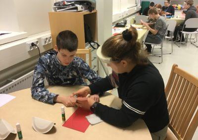 Opettaja auttaa opiskelijaa askartelussa.