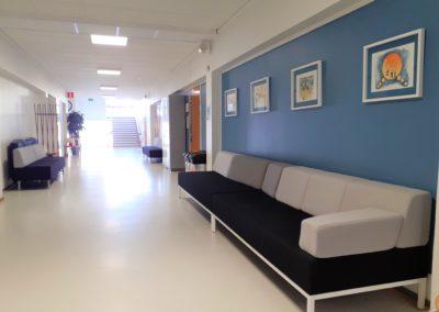 Toisen kerroksen käytävällä on sohvia ja seinällä on tauluja.