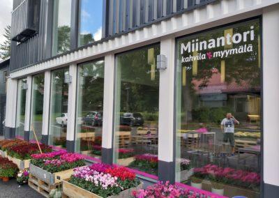 Miinantorin kahvilamyymälän ikkunat. Kukkia edessä.