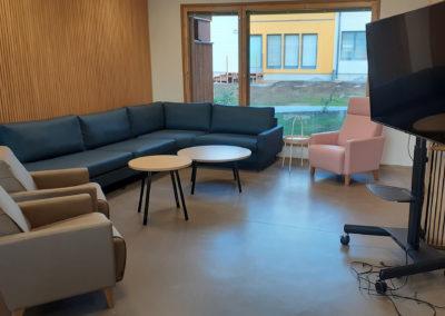 Oleskeluhuoneessa nojatuoleja, sohva, sohvapöytä, televisio.