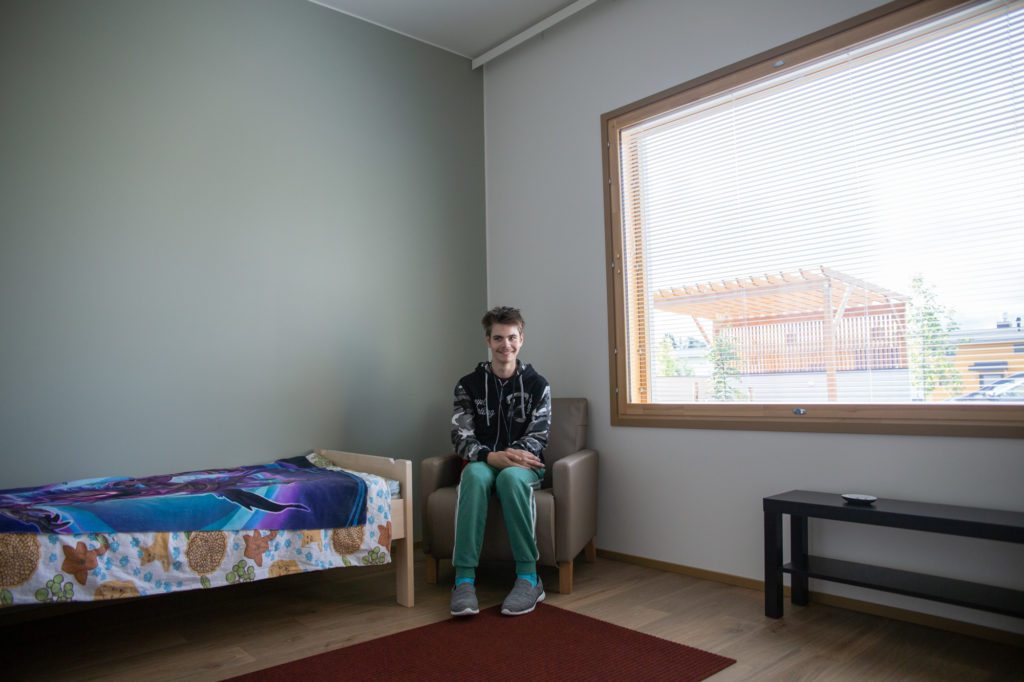 Opiskelija istuu nojatuolissa huoneessaan ja hymyilee.